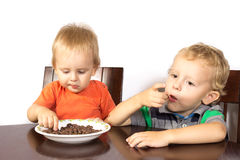 Two blonde brothers eat a race nuts Royalty Free Stock Photos