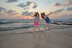 Two blonde girl jumping on the beach at sunset Stock Photography
