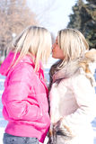 Two blonde girlfriends kiss Royalty Free Stock Photography