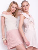 Two blonde girls in dresses in studio Royalty Free Stock Image