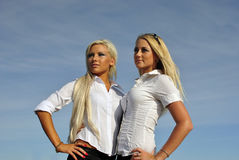 Two blonde girls on sky background Royalty Free Stock Images
