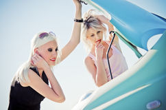 Two blonde girls stand by the broken car Royalty Free Stock Images