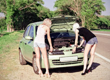 Two blonde girls standing by the broken car Royalty Free Stock Photography
