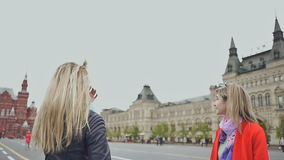 Two blonde girls tourists are hugging and smiling at the camera in Moscow Russia Red Square. stock video