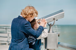 Two blonde hair brothers looks together in binoculars on the sea Stock Photo