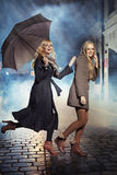Two blonde ladies running during rain Stock Photo