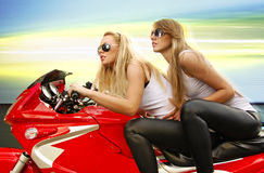 Two blonde on a motorcycle. Two pretty blonde woman on a big red motorcycle royalty free stock image