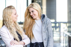 Two blonde students friends laughing using mobile phone and tablet Royalty Free Stock Image
