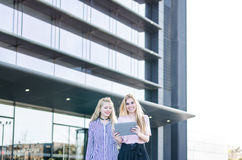 Two blonde students friends laughing using mobile phone and tablet Stock Images