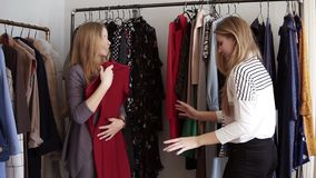 Two blonde twin sisters are shopping together. One trying the trendy dress or suit and offer to try it to her sister. Standing in front the rack with clothes stock video