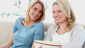 Two blonde watching TV. While sitting on a sofa stock video