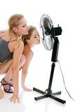 Two blonde woman under fan breeze Stock Photography