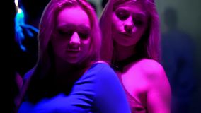 Two blonde women enjoying dance in night club, young people relaxing at disco. Stock photo stock photography