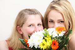 Two blonde women with flowers Stock Photos