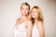 Two blonde women with no makeup on gray Stock Image