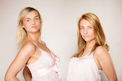 Two blonde women with no makeup on gray Stock Photo