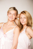 Two blonde women with no makeup on gray Stock Photos