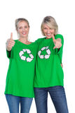 Two blonde women wearing green recycling tshirts giving thumbs u Royalty Free Stock Photo