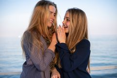 Two blonde young girls whispering to each other near the calm sea.  royalty free stock photo