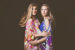 Two blonde young women beauty fashion portrait in colorful silky Stock Photography