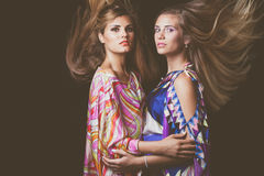Two blonde young women beauty fashion portrait with hair in motion. In colorful silky dress studio shot stock images