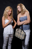 Two blondes look in the cell phone Stock Image