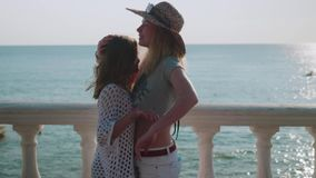 Two blondes put up and hug on the background of the sea and sunset. Two blondes are putting up and hugging in the background is the sea and the sunset stock video footage