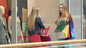 Two blondes on shopping discuss something very stock video
