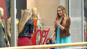 Two blondes on shopping discuss something very stock video footage