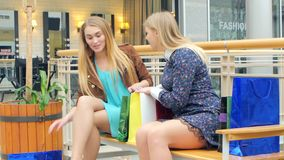 Two blondes sitting on a bench talking, bragging. Two, beautiful woman standing in big shop. Holding bags, smiling and talking by mobile phone stock video