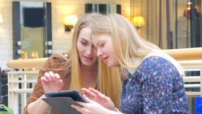 Two blondes sitting on a bench talking, bragging. Two, beautiful woman standing in big shop. Holding bags, smiling and talking by mobile phone. CLose Up stock footage