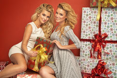 Two blondies on the Christmas gifts Stock Photography