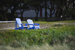 Two Blue  Adirondack Chairs on a Beach Stock Image
