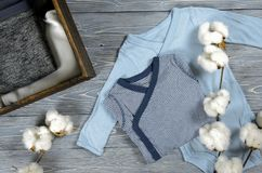 Two blue babies bodysuits on gray wooden background. Shopping ma Stock Photos