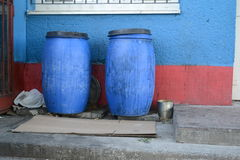 Two blue barrels in backyard Royalty Free Stock Image