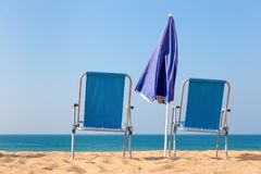 Two blue beach chairs and parasol at sea Stock Image