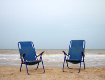 Two blue beach chairs on the sand near the sea. Two blue beach chairs on the beach near the sea, eventide Royalty Free Stock Image