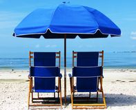 Two Blue Beach Chairs and Umbrella on the Beach. Blue beach chairs and umbrella on the sand by the ocean Royalty Free Stock Photos