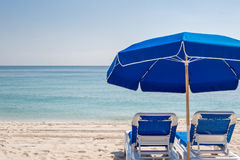 Two blue beach lounge chairs under a blue umbrella & blue skies looking out from beach to ocean. Stock Photos