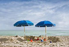 Two blue beach umbrellas and toys Stock Photography