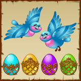 Two blue birds with colored eggs in a golden stand Stock Images