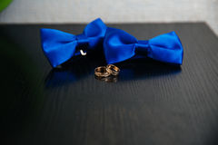 Two blue bow tie and golden wedding rings on black background. Concept of clothes. Two blue bow tie and golden wedding rings on black background Royalty Free Stock Image