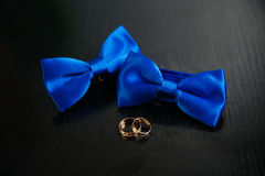 Two blue bow tie and golden wedding rings on black background. Concept of clothes. Two blue bow tie and golden wedding rings on black background Stock Image