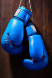 Two blue boxing gloves hanging against wooden background. Vertical photo of the bright sportwear against brown wall. Boxing exercise and training. Energy Stock Photography