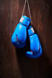 Two blue boxing gloves hanging against wooden background. Royalty Free Stock Photo