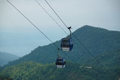 Two blue cable car cabines with a mountain in the background stock photo