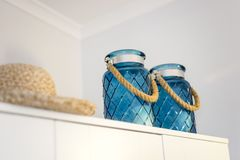 Two, blue candlestick jars with summer hat nicely decorating a w. Ardrobe in the bedroom Stock Photography
