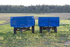 Two blue carts for tractors are in the garden in the village stock photo