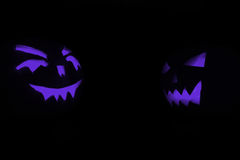 Two blue carved face of pumpkin glowing on Halloween black background Royalty Free Stock Photos