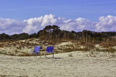 Two blue chairs in front of a sand dune on the bea Stock Images